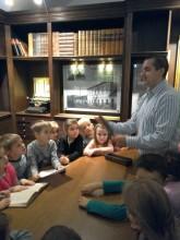 Przewodnik opowiada dzieciom o dawnej szkole.